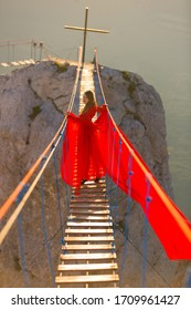 A young girl in a red dress high in the mountains on a suspension bridge