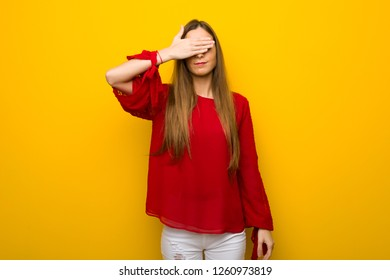 Young girl with red dress over yellow wall covering eyes by hands. Do not want to see something