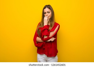 Young girl with red dress over yellow wall having doubts