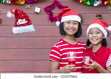 Young girl in red dress shows a smile face and drinking red juice in Christmas Day. She wears a Santa Claus's hat to celebrate tonight. Soft focus and blur. Holiday concept.