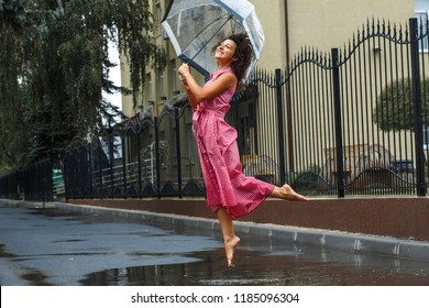Young girl in a red dress with a transparent umbrella dancing in the rain standing in a puddle.