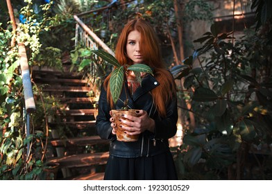 young girl with red hair and blue eyes in a black jacket in a tropical forest. beautiful botanical garden.