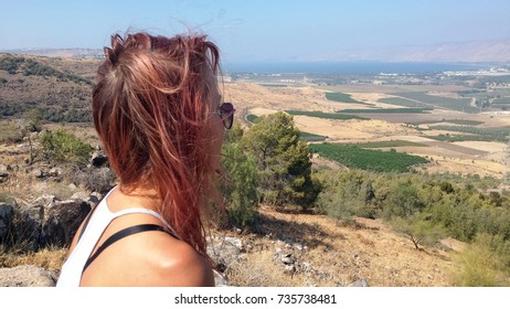 Young girl with red hair and sunglasses looking at the valley, Israel