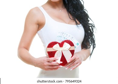 Young girl with red heart-shaped gift box with Russian money in white dress on white background