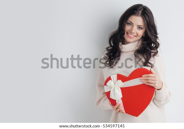 白い背景に赤いハートの形のギフトボックスを持つ若い女の子