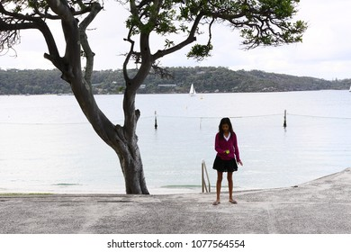 Young girl with red jumper standing next to a tree by the sea at shark beach in Sydney