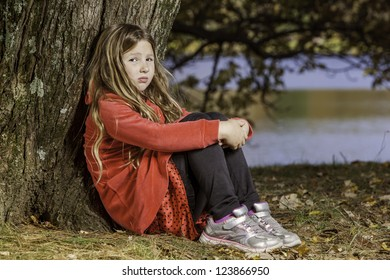 young girl, in red outfit leaning against a tree. A look of sadness or thought on her face, close up full body shot with lake in the background blurred.