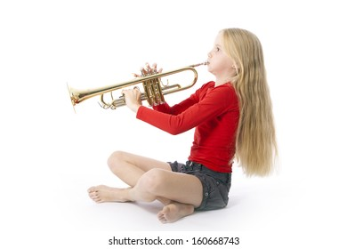 young girl in red playing trumpet against white background