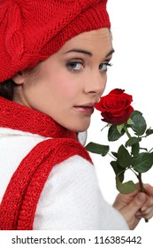 young girl with red rose and assorted winter clothing