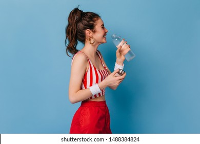 Young girl in red striped outfit laughs and drinks water from bottle on isolated background