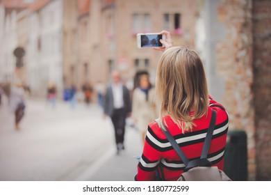 young girl in red sweater at streets of Bruges. Belgium, Atumn season