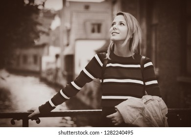 young girl in red sweater at streets of Bruges. Belgium, Atumn season Image in sepia color style