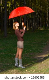 The young girl with a red umbrella in autumn park