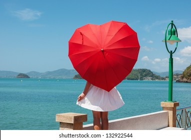 young girl with a red umbrella on the waterfront
