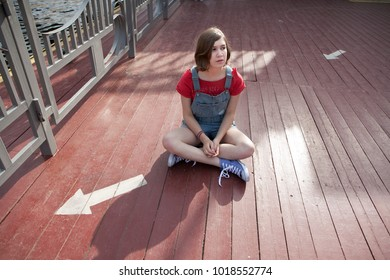 A young girl in a red wool sweater and jeans shorts is sitting on the steps