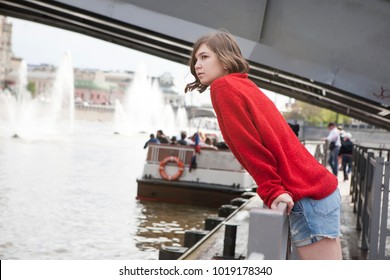 A young girl in a red wool sweater and jeans shorts . She leaned against the railing beside the canal