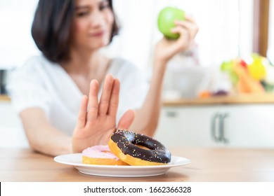 Young girl rejecting junk food or unhealthy food such as donuts and choosing healthy food such as a green apple and salad for having a good health. Dieting and good health concept.