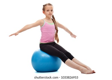 Young girl relaxing after workout - sitting on large gymnastic rubber ball, isolated