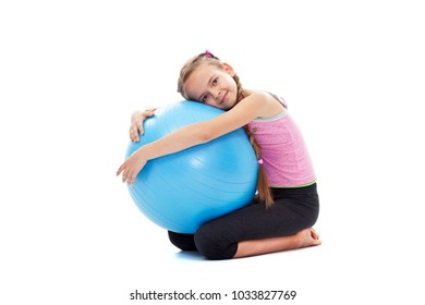 Young girl relaxing after workout - sitting and holding a large gymnastic rubber ball, isolated