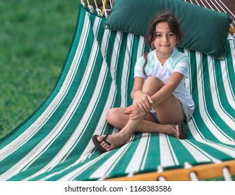 Young girl relaxing in green hommock