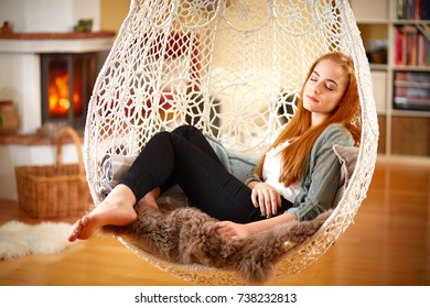 Young girl relaxing in a Hanging chair at home