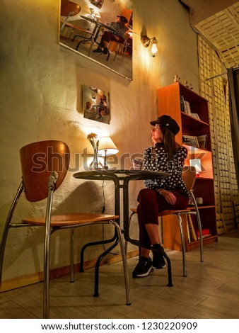 Young girl relaxing on a chair looking at a picture of a young  girl relaxing on a chair looking at a picture of a young girl relaxing on a chair looking at a picture.