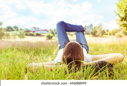 Young girl relaxing on grass field.  People, nature, relaxation.