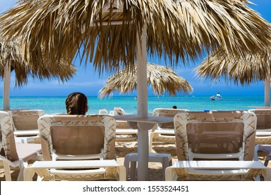 Young girl relaxing on lounger under palm tree leaves umbrella on the beach against turquoise water of sea, Punta Cana, Dominican Republic