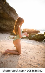 Young girl relaxing on a tropical beach at sunset