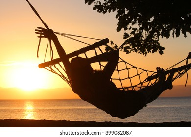 Young girl resting in a hammock overlooking the sea