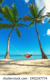 Young girl resting in a hammock under tall palm trees, tropical beach