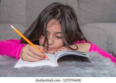A young girl is resting her head in a book while doing her homework