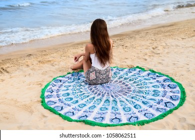 young girl resting on the beach lying on a towel