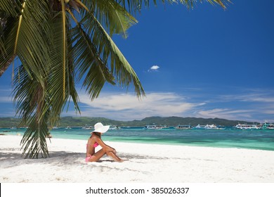 young girl resting on the beach under a palm tree