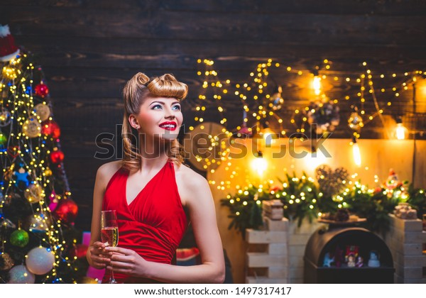 Young girl with retro hairstyle and pinup makeup over Christmas tree. Christmas Party drinks and holidays people concept. New year fashion clothes