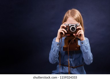 Young girl with retro photo camera. Beautiful smiling child (kid, girl) holding a instant camera