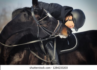 Young girl rider kissing her horse