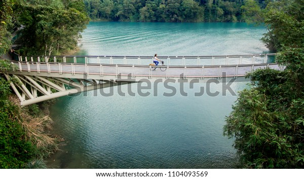 Young girl riding bicycle on the bridge at Sun Moon Lake, Nantou, Taiwan