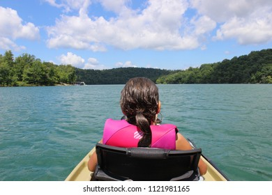 Young girl riding in front of a kayak with scenic forest and lake views