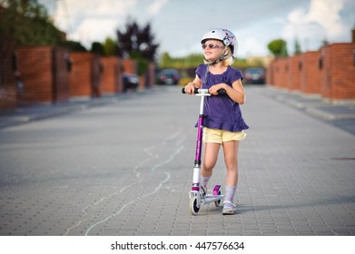 Young girl riding her scooter