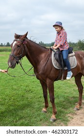 Young girl riding horse with instructor help