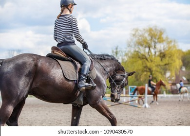 Young girl riding horse on her course in training show jumping. Equestrian sport training background