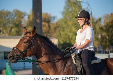 Young Girl riding horse at sunset. equitation. Riding young woman on horse in outdoor. Beautiful smiling young woman close-up with horse, against green of summer park. Horse and jockey