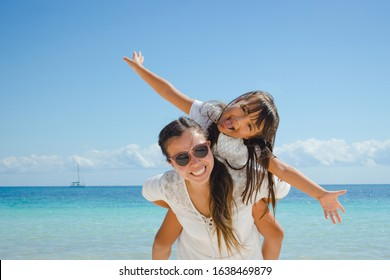 Young girl riding on piggy back on her mother with the caribbean sea on the background.