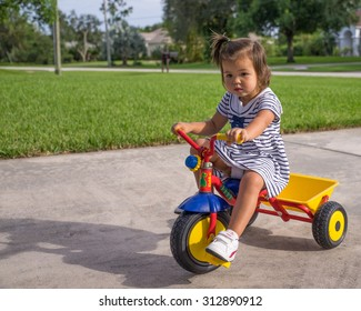 Young Girl Riding Tricycle