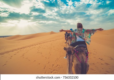 Young girl rising arms while riding camel in the middle of the desert