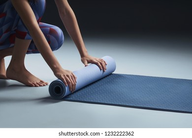 Young girl rolling mat after a yoga class. Close up, solid dark background, copy space.