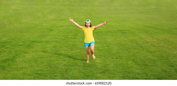 Young girl run on the background of green grass