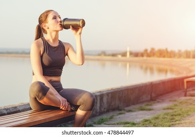 Young girl running after sitting on the bench. Sportswoman drinks from the shaker.