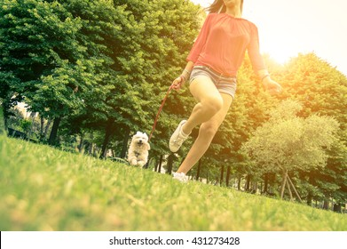 Young girl running with her dog. Puppy white dog is running with it's owner. Concept about friendship, animal and freedom